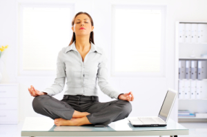 Young businesswoman sitting at table with yoga and meditation.